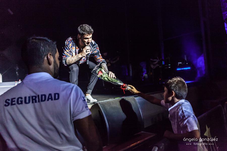 Foto de Melendi cojiendo regalo de niño en el escenario